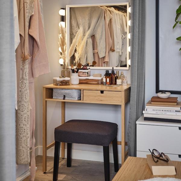 Un miroir carré, une coiffeuse en bambou, deux appliques LED et un tabouret gris foncé forment un coin beauté complet.