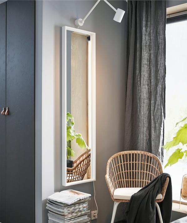 Un miroir en pied sur un mur gris, fauteuil en rotin et pile de magazines.