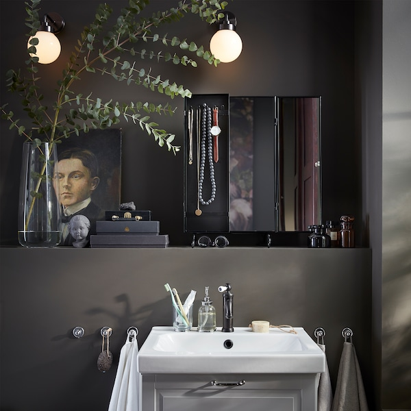 Un miroir noir, un vase avec une branche d'eucalyptus, deux appliques murales rondes et un lavabo blanc.