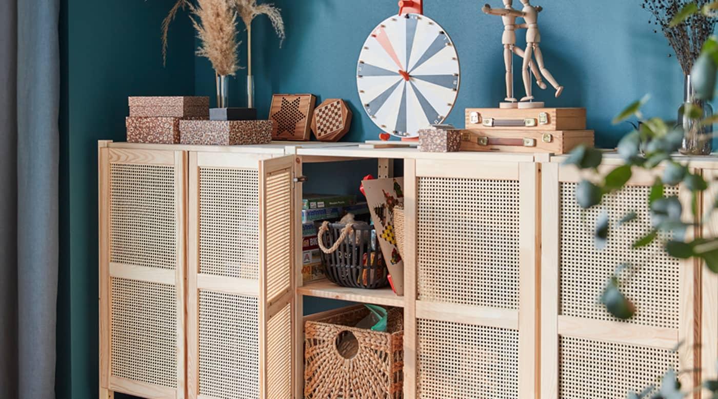 Un mobile a parete con ante a reticolo, di cui una aperta mostra i contenitori al suo interno, e accessori e altri contenitori sul ripiano superiore - IKEA