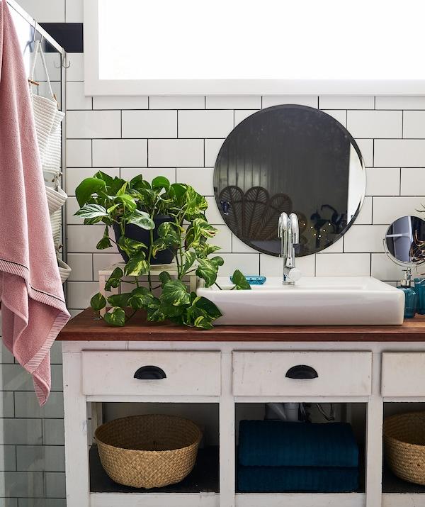 Un mobile in legno con lavabo grande bianco, una pianta e uno specchio rotondo su una parete con piastrelle bianche - IKEA