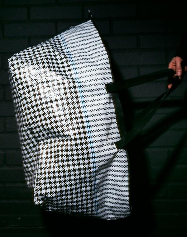 Un model subjecta la bossa SAMMANKOPPLA en una habitació fosca. El flaix de la càmera ressalta la seva textura lluent i el disseny de quadres.