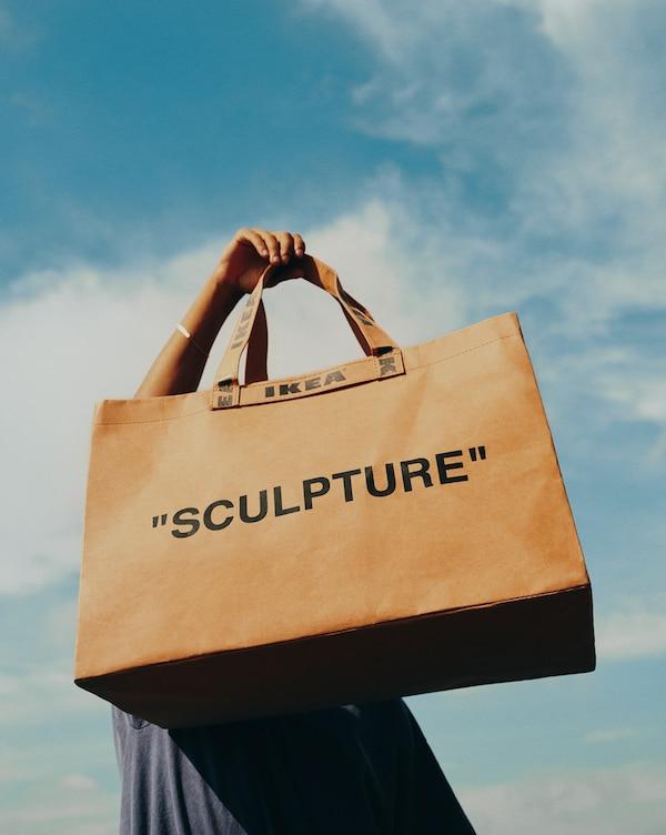 """Un modelo levanta no aire unha bolsa IKEA marrón coa palabra """"SCULPTURE"""" escrita."""