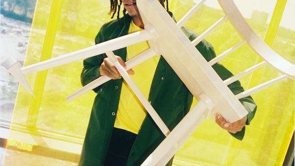 Un modelo sostiene una silla de madera ante la cámara, mostrando el tope de puerta unido a una de sus patas delanteras.