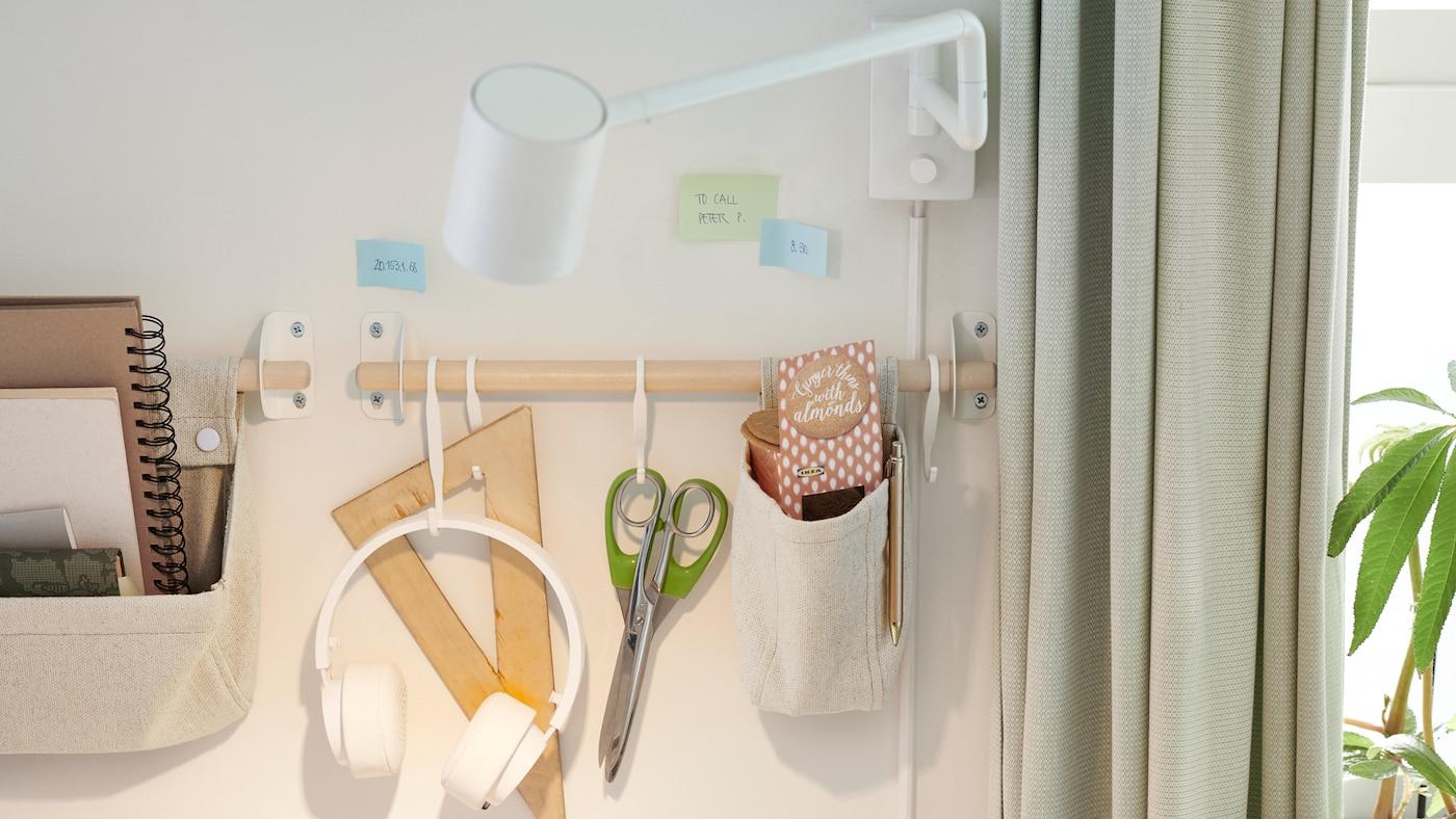 Un mur avec une applique NYMÅNE blanche. Des fournitures de bureau sont suspendues à des crochets et rangées dans des récipients NEREBY en chanvre fixés à un rail en bouleau.