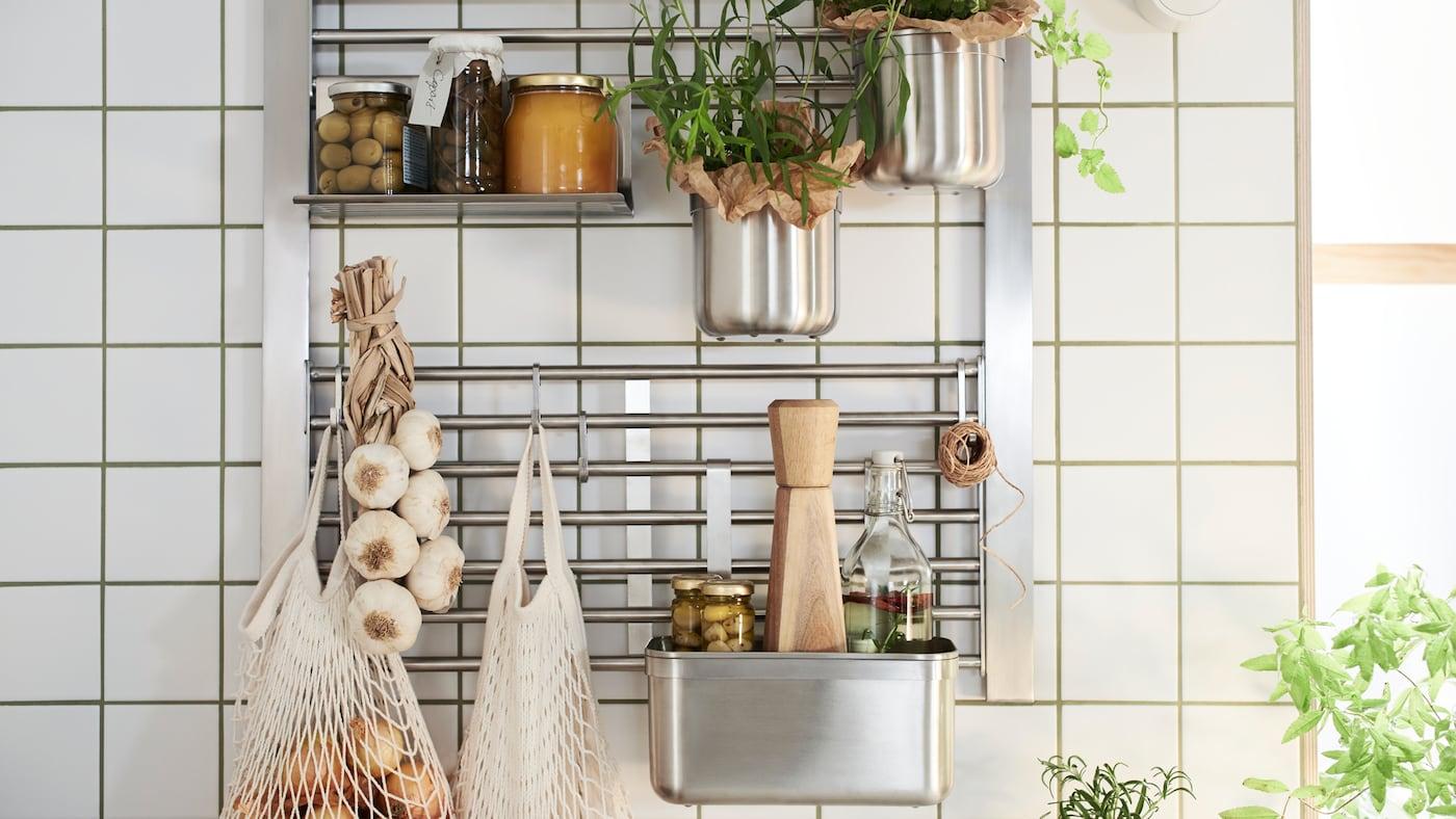 Un mur de cuisine avec une grille murale KUNGSFORS dotée d'une étagère, de crochets et de récipients, le tout en acier inoxydable, où sont rangés des bocaux et des herbes aromatiques.
