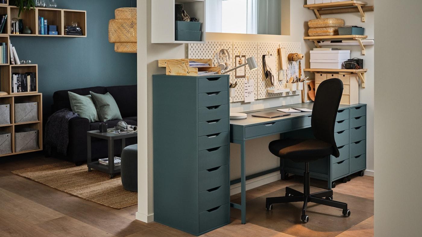 Un mur séparant un séjour d'un espace de travail à la maison, un bureau et des blocs tiroirs gris-turquoise, une chaise de bureau noire.