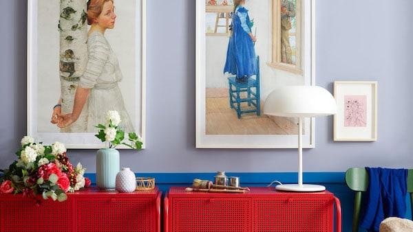 Un mur sur lequel sont accrochés des cadres pour photos et quelques rangements rouges avec une lampe, des plantes et un vase STILREN avec une fleur.