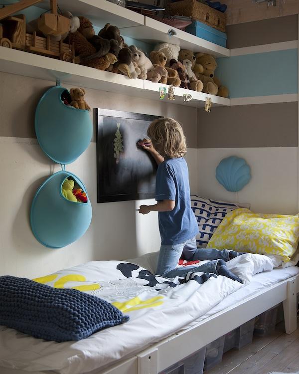Un niño arrodillado en una cama mientras dibuja en una pizarra montada en la pared de su dormitorio.