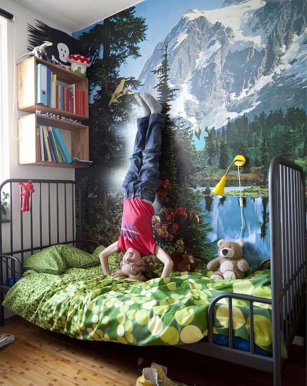 Un niño hace el pino en una cama y apoya los pies contra la pared con un paisaje de montaña.