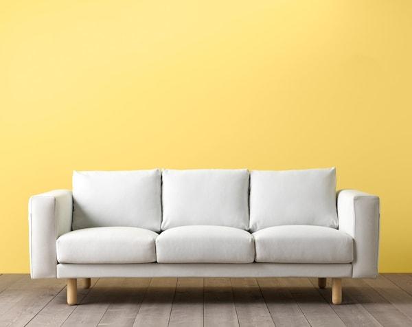 Un nuevo sofá de tres plazas de IKEA frente a una pared amarilla en la exposición para que los clientes puedan probarlo y ver cómo queda.