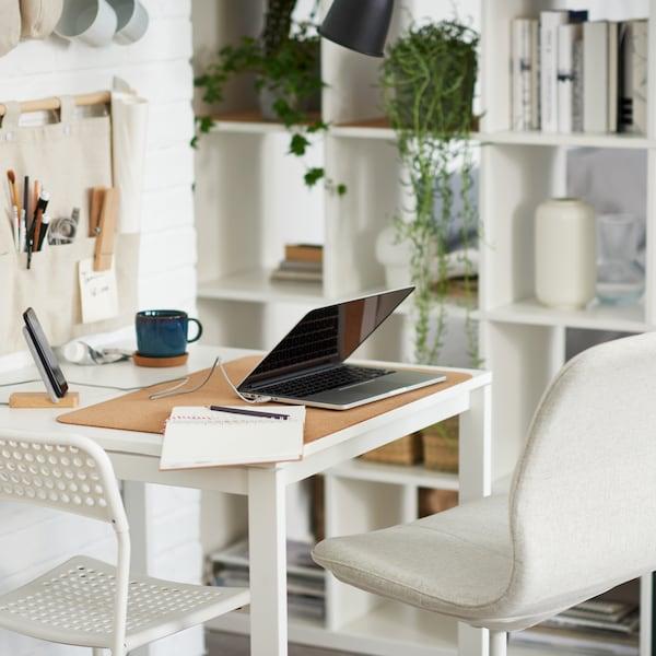 Un ordenador portátil sobre una mesa blanca con una silla de oficina blanca y otra beige, junto a una estantería blanca con libros y espacio de almacenaje.