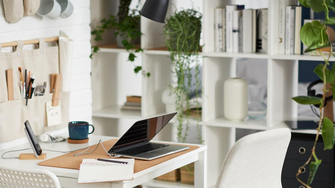Un ordinateur portable sur une table blanche avec une chaise blanche et une chaise beige, une étagère blanche accueillant des livres, des plantes et des rangements.