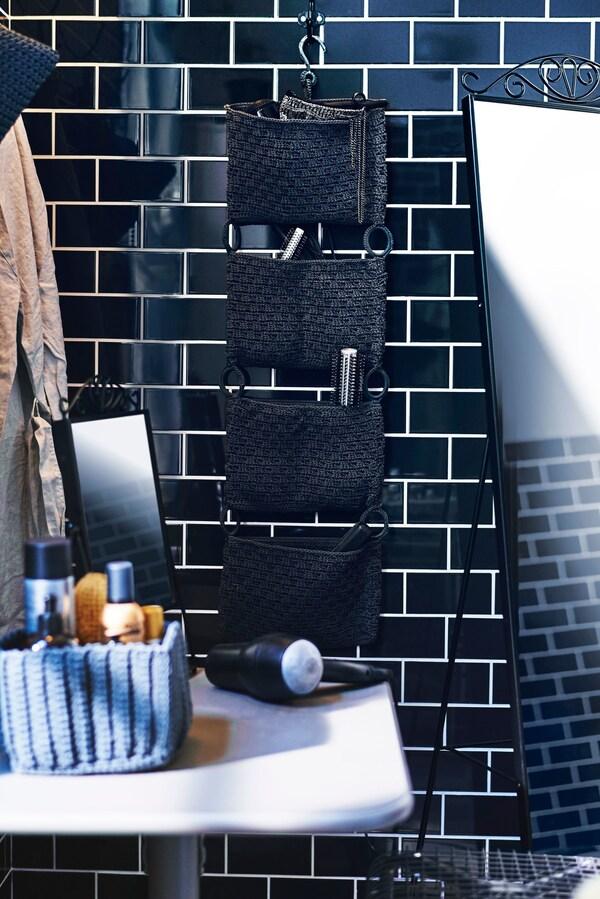 Un organizador de baño de pared con productos capilares, que cuelga de una pared de azulejos negros.