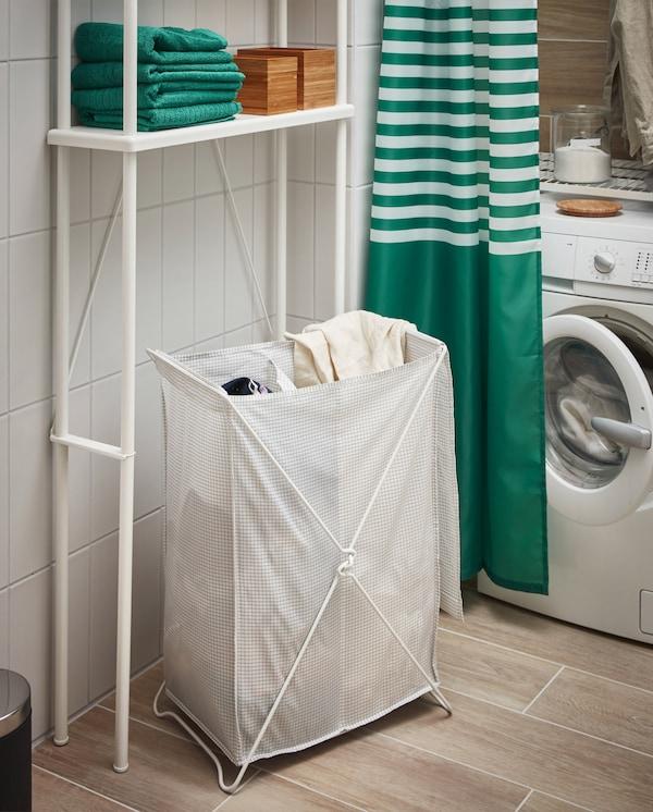 Un panier à linge blanc/gris, un lave-linge, un rideau de douche vert/blanc, des serviettes vertes et un rangement ouvert DYNAN blanc.
