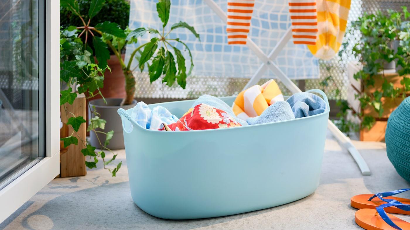 Un panier à linge souple TORKIS bleu rempli de linge, un étendoir et un pouf sur un balcon ensoleillé décoré de plantes.