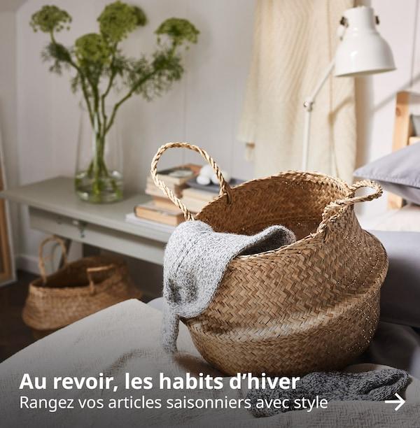 Un panier en jonc de mer avec une chaussette tricotée drapée sur le côté. Le texte sur l'image est le suivant : « Au revoir, les habits d'hiver. Rangez vos articles saisonniers avec style ».