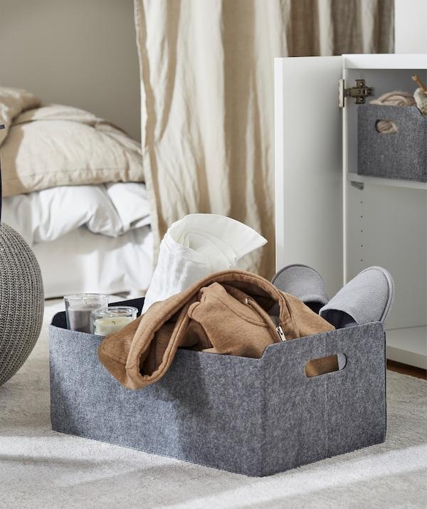Un panier rectangulaire en feutre sur un tapis dans une salle de séjour et dans lequel se trouve des bougies chauffe-plats, des pantoufles, une serviette et un pull à capuche.