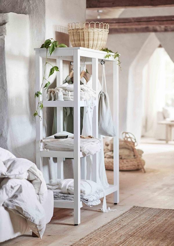 Un panier traditionnel en rotin se trouve sur une armoire-penderie ouverte blanche.