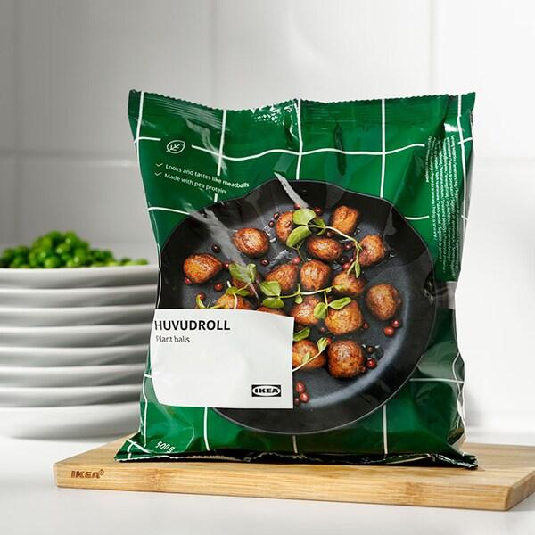 Un paquet de boulettes végétales HUVUDROLL sur une planche à découper en bambou reposant sur le dessus d'un comptoir blanc.