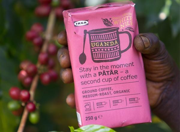 Un paquet rose de café PÅTÅR édition spéciale 100% Arabica dans la main d'un cultivateur de café.