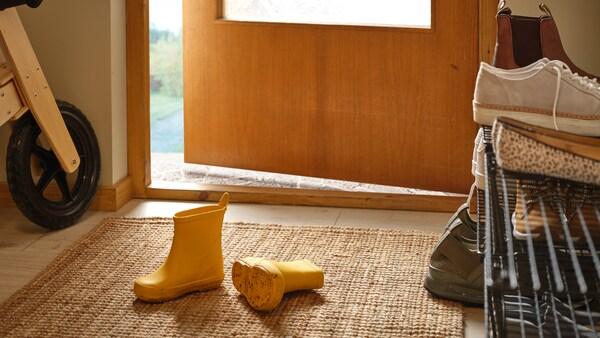 Un par de botas infantís amarelas sobre unha alfombra de tecido plano LOHALS nunha entrada, xusto a unha principal entreaberta.
