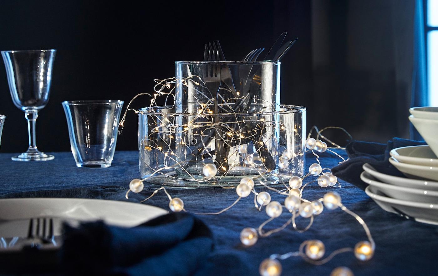 Un par de cadenas de iluminación LED de IKEA SNÖYRA yacen sobre una mesa entre vasos, vasos y platos.