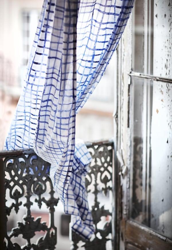 Un par de cortinas de algodón IKEA TÄNKVÄRD con un estampado a cuadros azules y blancos colgando de un balcón.