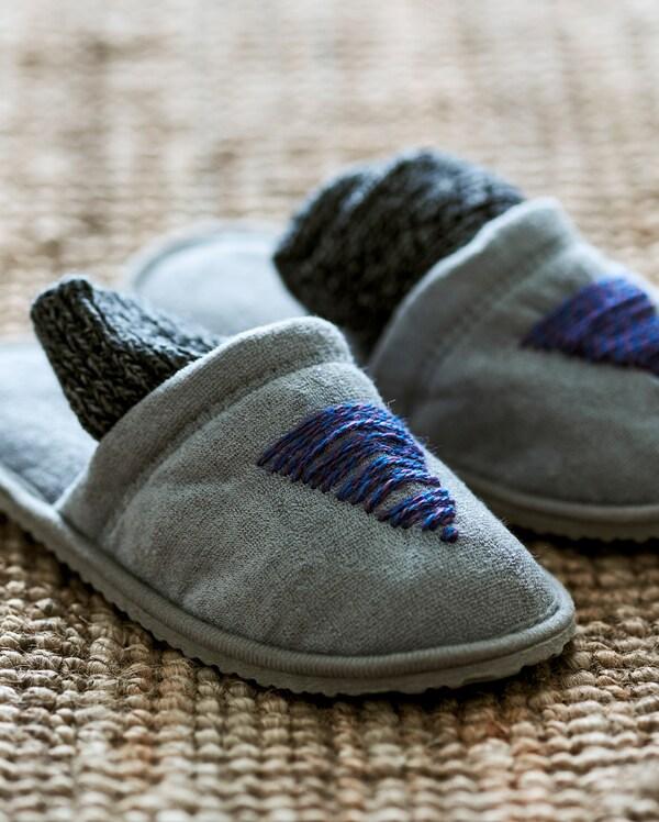 Un par de zapatillas grises sobre una alfombra de yute, personalizadas con hilo de lana azul que forma un motivo de abeto en la parte delantera.