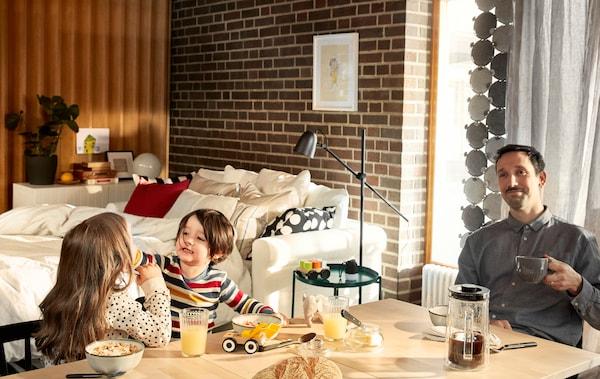 Un pare seu despreocupat a la taula de l'esmorzar amb una tassa de cafè a la mà mentre els seus dos fills juguen amb el menjar al seu costat.