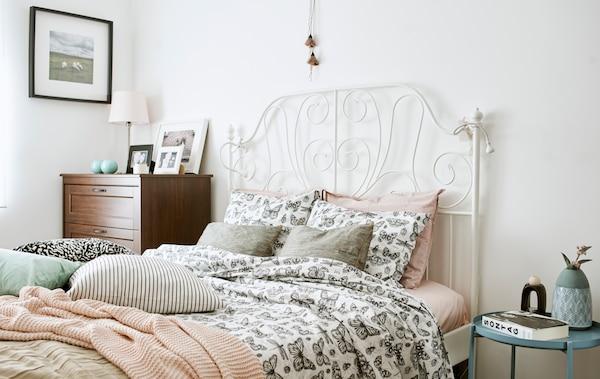 Un pat cu tăblie din fier forjat alb, îmbrăcat într-o cuvertură cu desene monocrome cu fluturi, o pătură tricotată roz și perne.