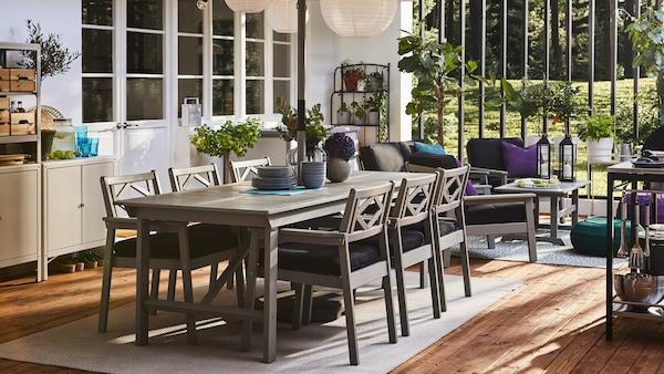Un patio avec une table et des chaises à accoudoirs en gris, un rangement, des suspensions rondes et un sol en bois.