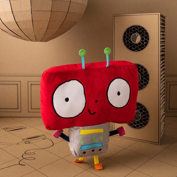 Un peluche de robot IKEA SAGOSKATT sonriente y bailarín con una cabeza grande, roja y cuadrada con antenas.