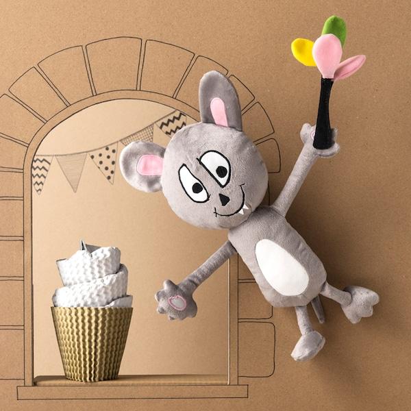Un peluche IKEA SAGOSKATT gris y blanco: un alegre ratón con globos volando delante de un castillo de cartón.