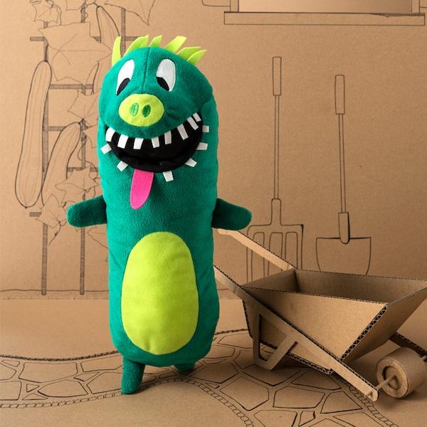 Un peluche IKEA SAGOSKATT que es un pepino superhéroe de color verde con pelo, dientes y lengua rosa.