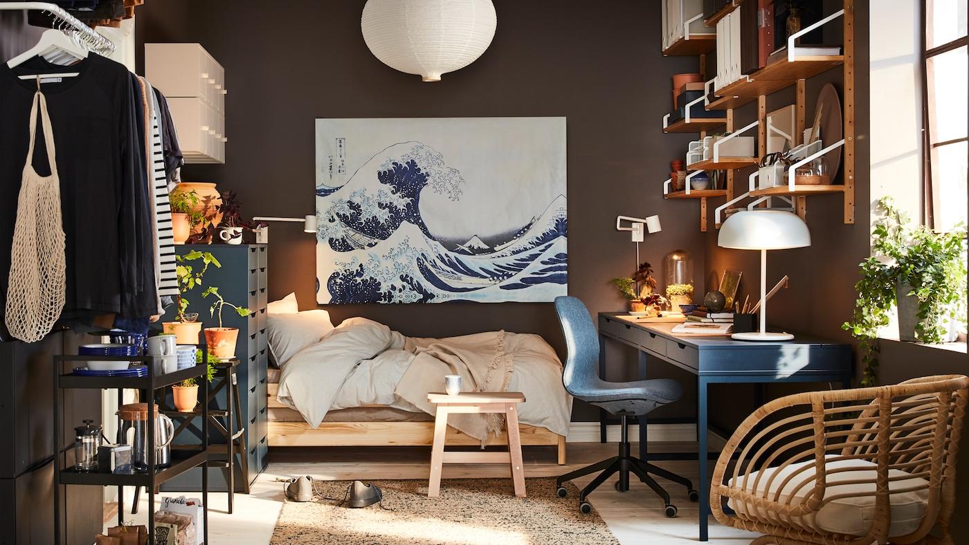 Un pequeño hogar con un escritorio azul oscuro, un sillón de ratán, una lámpara de techo blanca y un cuadro con una ola azul.