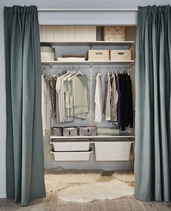 Un pequeño vestidor hecho de estantes, rieles y cajones ALGOT ajustables y abiertos, rematado con algunas alfombras.