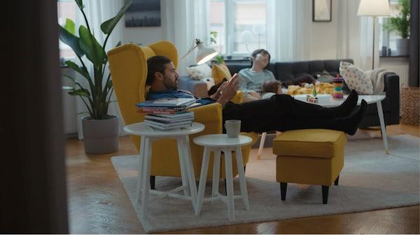 Un père se détend dans un canapé jaune tandis que son fils est allongé, épuisé, dans le canapé.