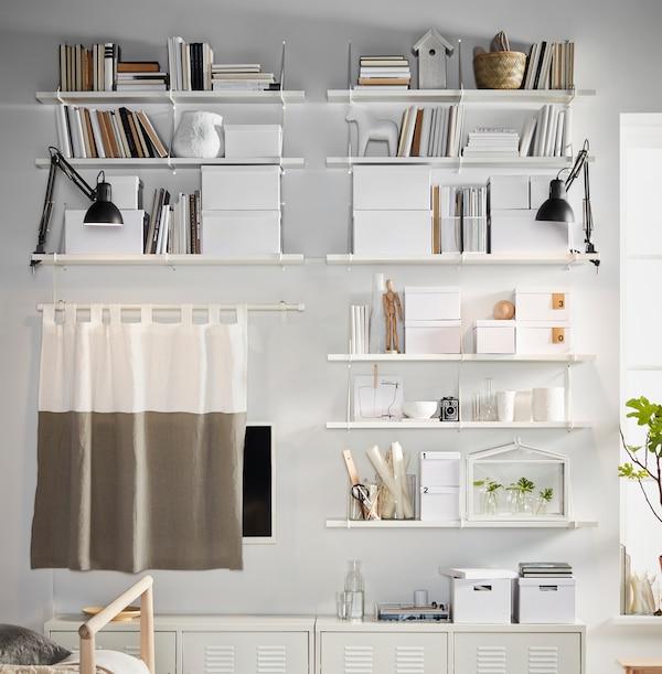 Un perete alb plin cu polițe, cutii de depozitare TJENA și corpuri IKEA PS, toate albe și dispuse simetric.