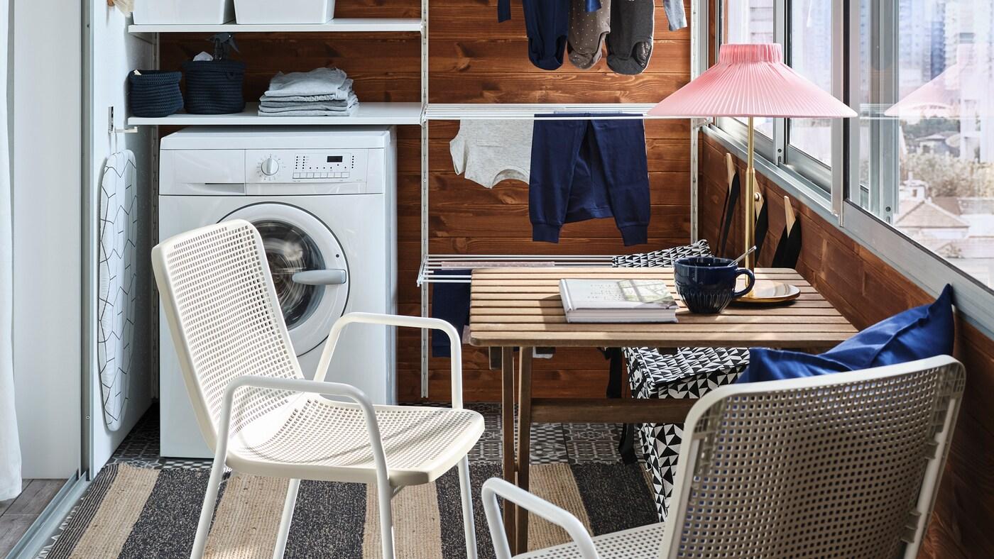 Un petit balcon avec un rangement modulaire blanc pour la lessive, une machine à laver, une petite table et deuxchaises blanches/beiges.