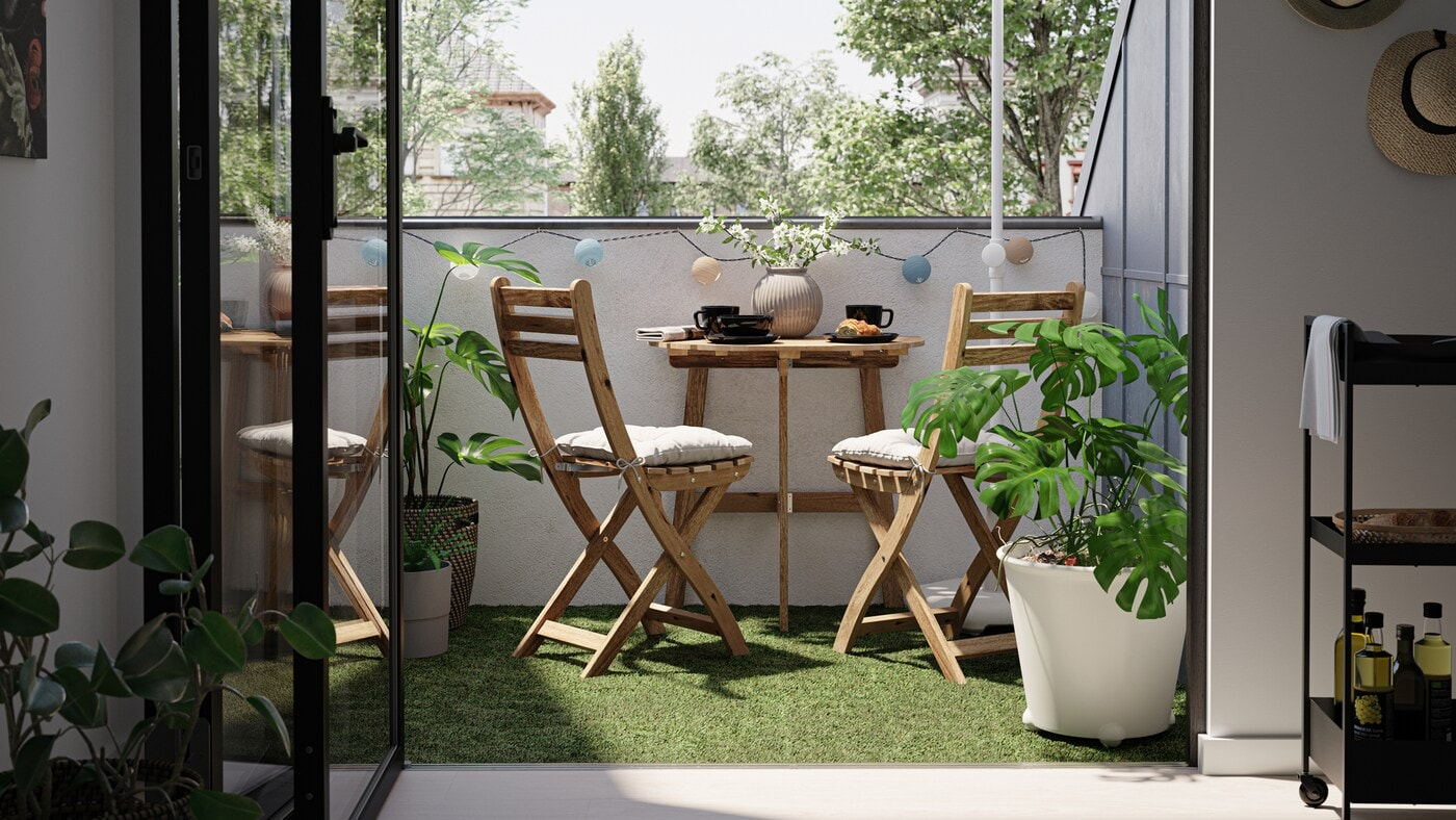 Un petit balcon avec une table et des chaises en bois, un gazon artificiel et une plante monstera dans un cache-pot blanc.