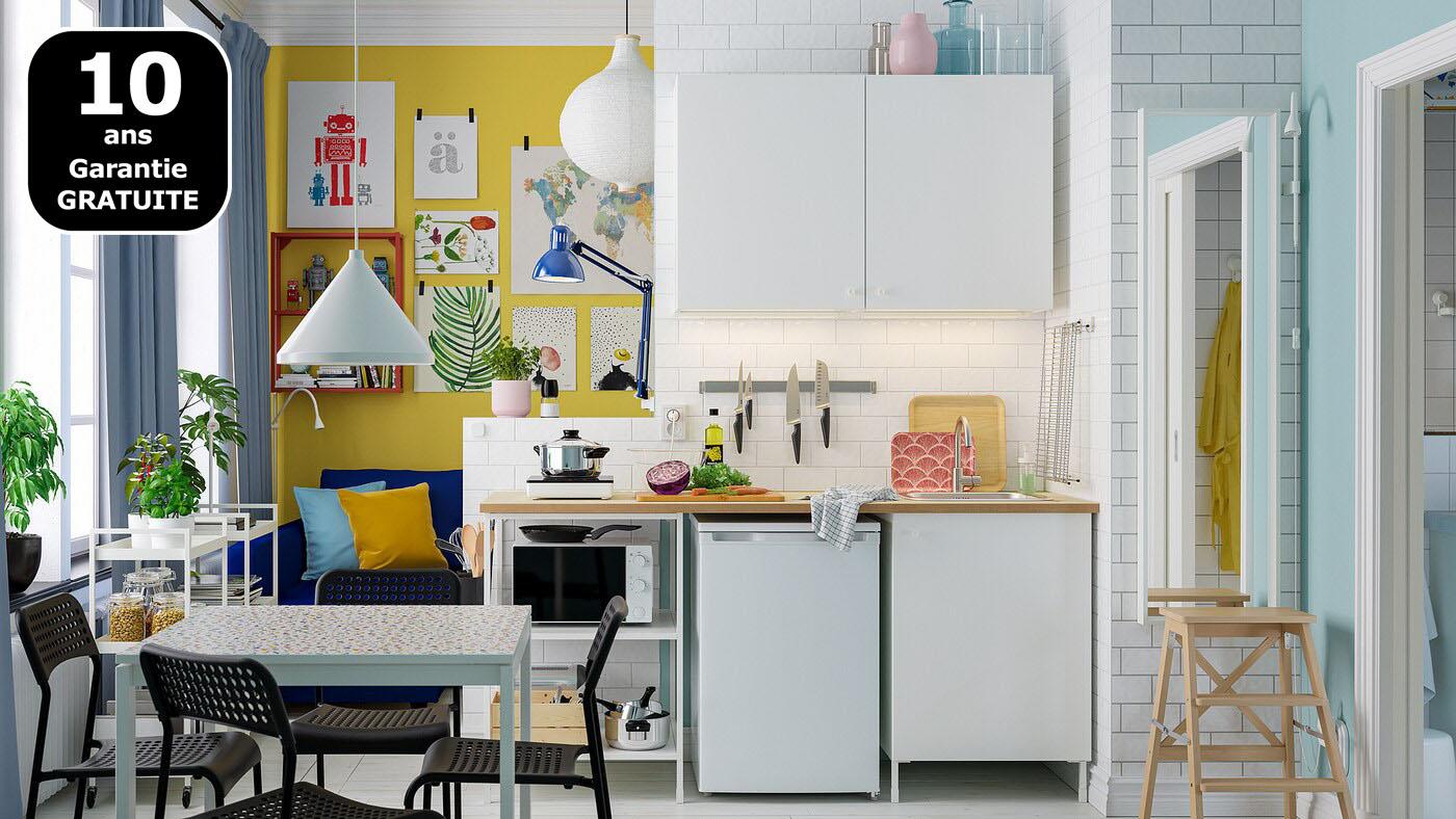 Un petit coin cuisine lumineux aménagé avec une combinaison de cuisine ENHET blanche, une table blanche et quatre chaises noires.