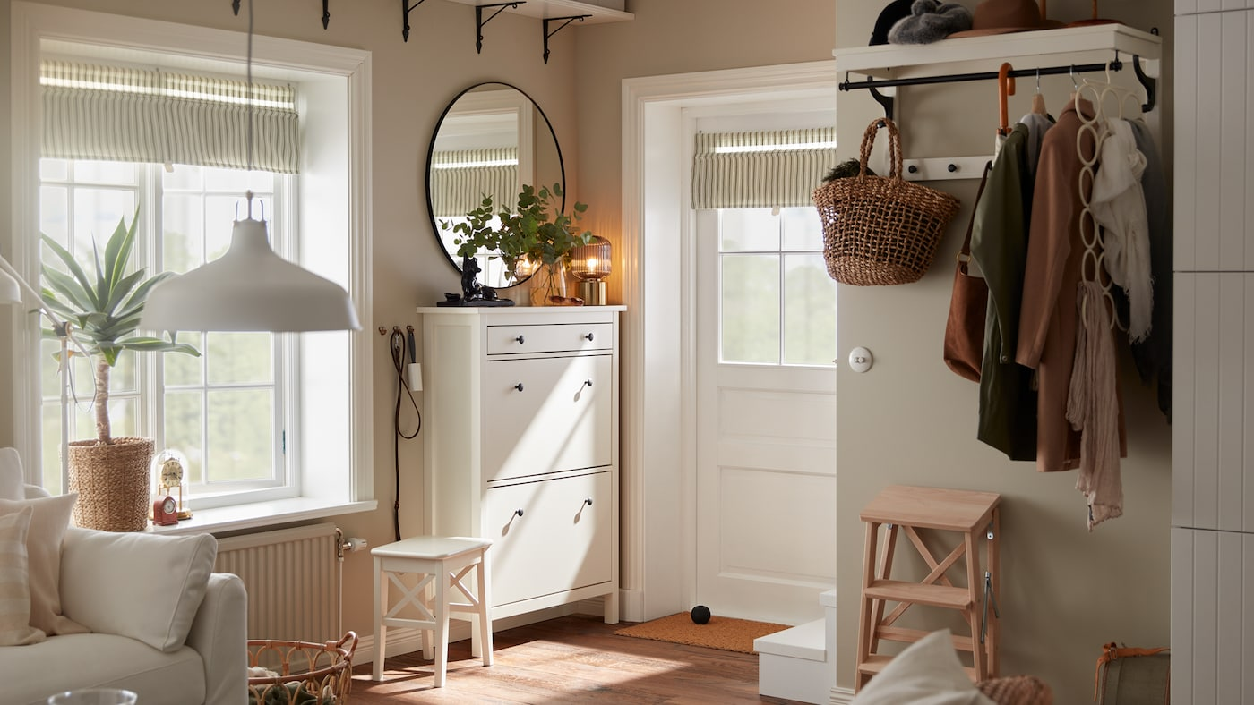 Un petit hall d'entrée avec une porte blanche, une armoire à chaussures blanche, un miroir rond, une étagère à chapeaux blanche où sont suspendus des manteaux.