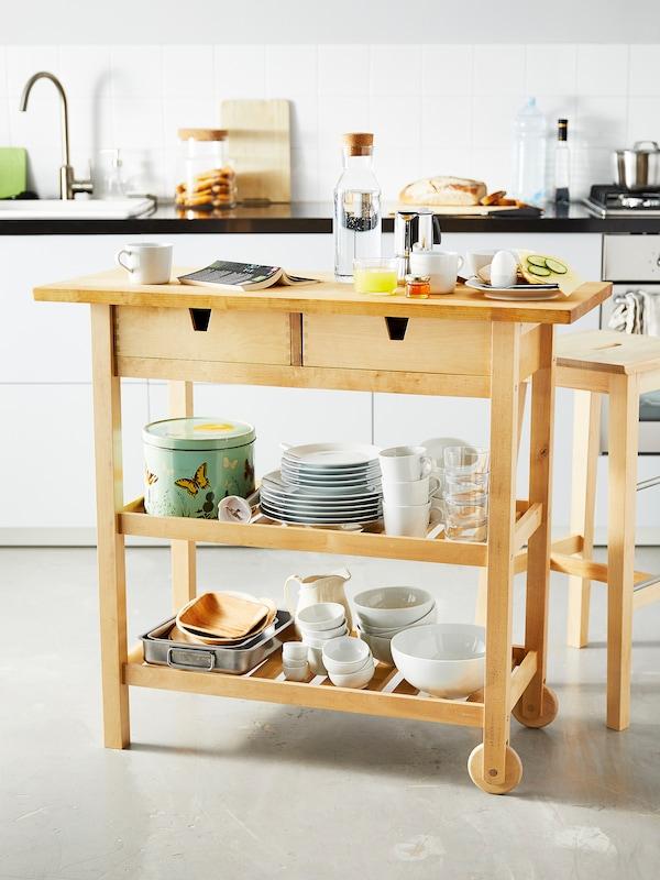 Un petit îlot de cuisine en bois avec des aliments pour le petit déjeuner sur le dessus et de la vaisselle rangée sur les tablettes.