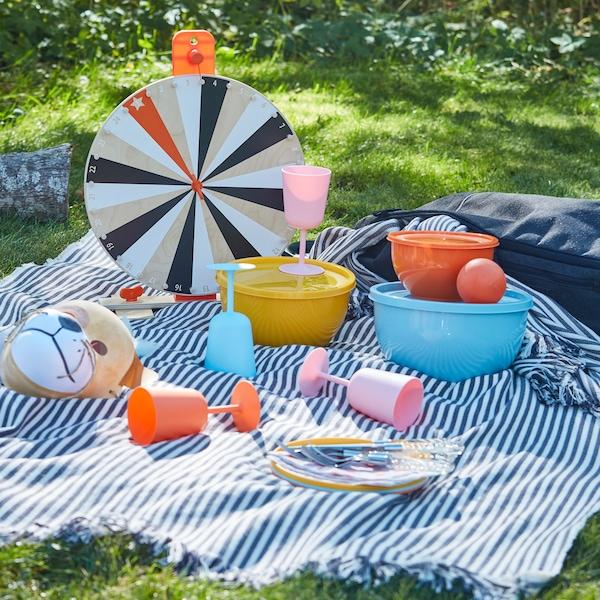 Un pícnic en la hierba con vajilla y copas de plástico en colores variados.