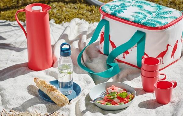 Un pique-nique installé sur un plaid blanc sur l'herbe, avec un sac isotherme SOMMARLIV, des mugs TALRIKA et une salade légère dans une assiette TALRIKA.