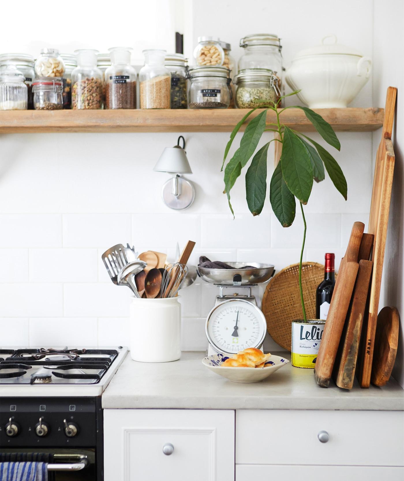 Un plan de travail avec une cuisinière et des planches en bois, et des bocaux remplis d'ingrédients secs disposés sur une tablette en bois au-dessus.