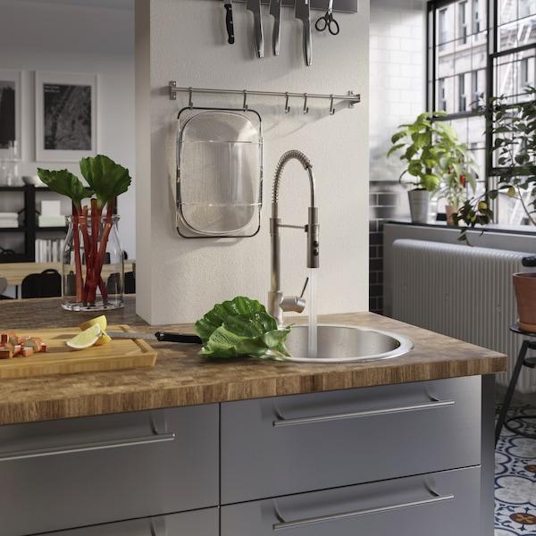 Un plan de travail en bois, un évier encastré et un robinet mitigeur avec douchette, dont le jet lave la rhubarbe dans l'évier.