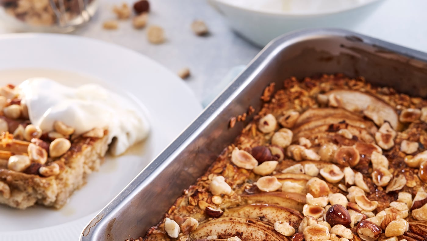 Un plat à four contenant un porridge HJÄLTEROLL prêt à côté d'une assiette blanche avec une tranche de porridge et une cuillerée de yaourt dessus.