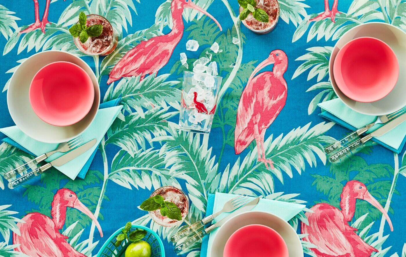Un plateau de table avec une nappe en tissu aux motifs tropicaux colorés en rose, vert et bleu. Une vaisselle assortie est posée sur la table.